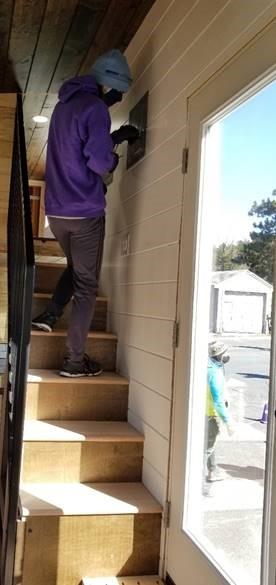 Student on steps inside tiny house.